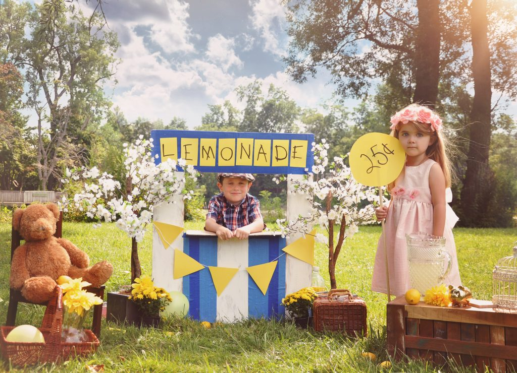 Starting a business - from the lemonade stand to a multi million dollar company. Two little kids are selling lemonade at a homemade lemonade stand on a sunny day with a price sign for an entrepreneur concept